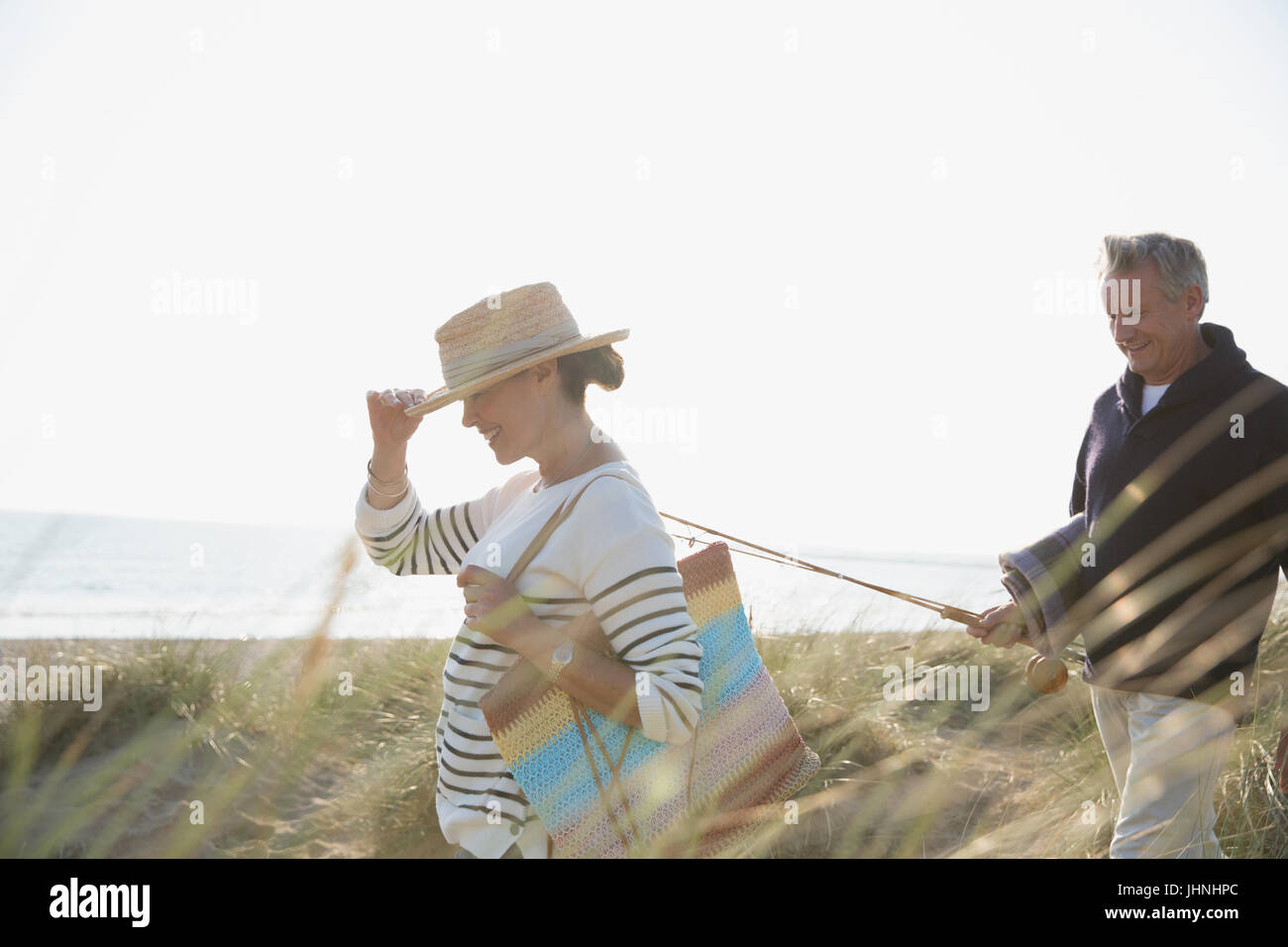 Mature couple with fishing rod walking in sunny summer beach grass - Stock Image