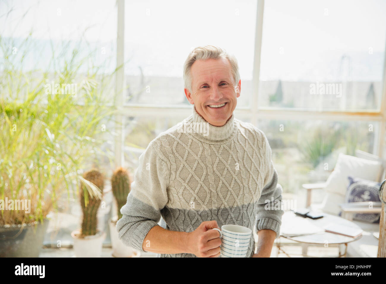 Portrait smiling senior man drinking coffee in beach house sunny sun porch - Stock Image