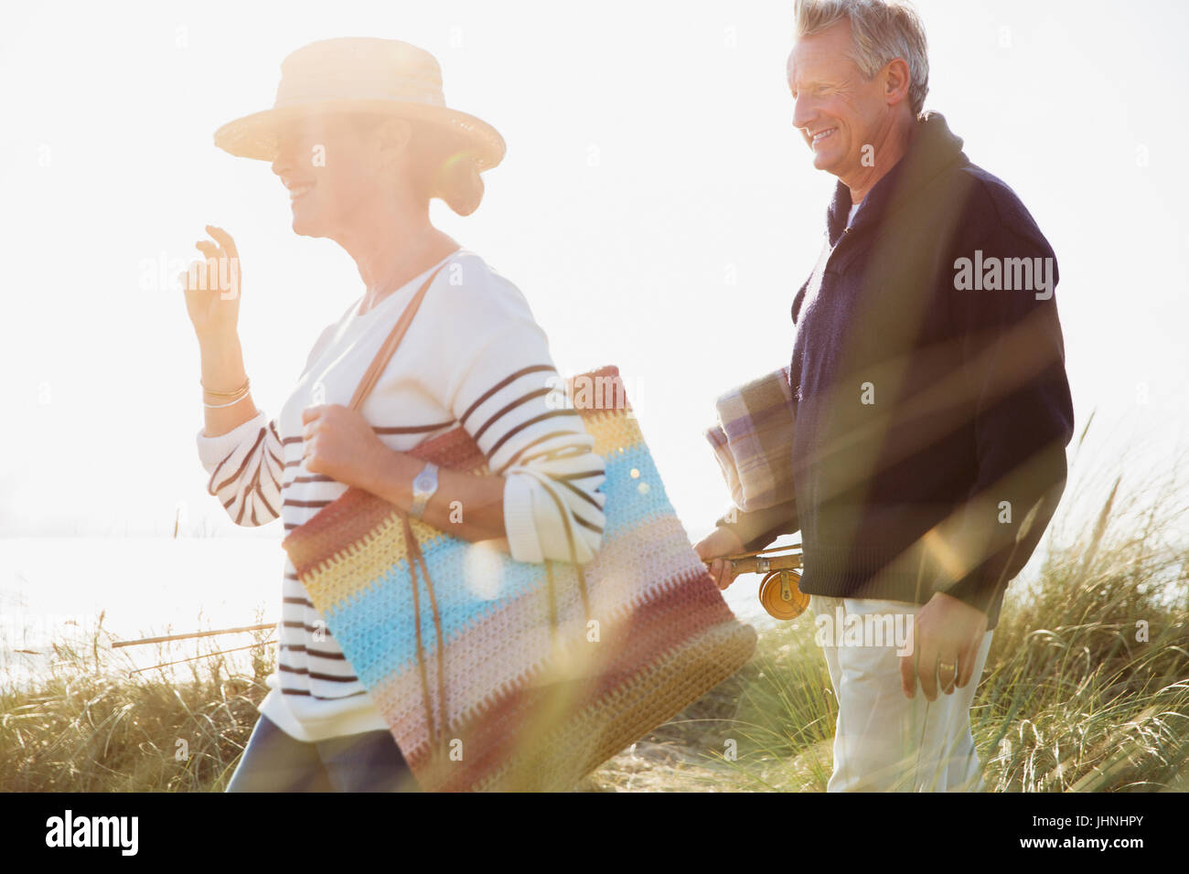 Mature couple walking in sunny beach grass - Stock Image