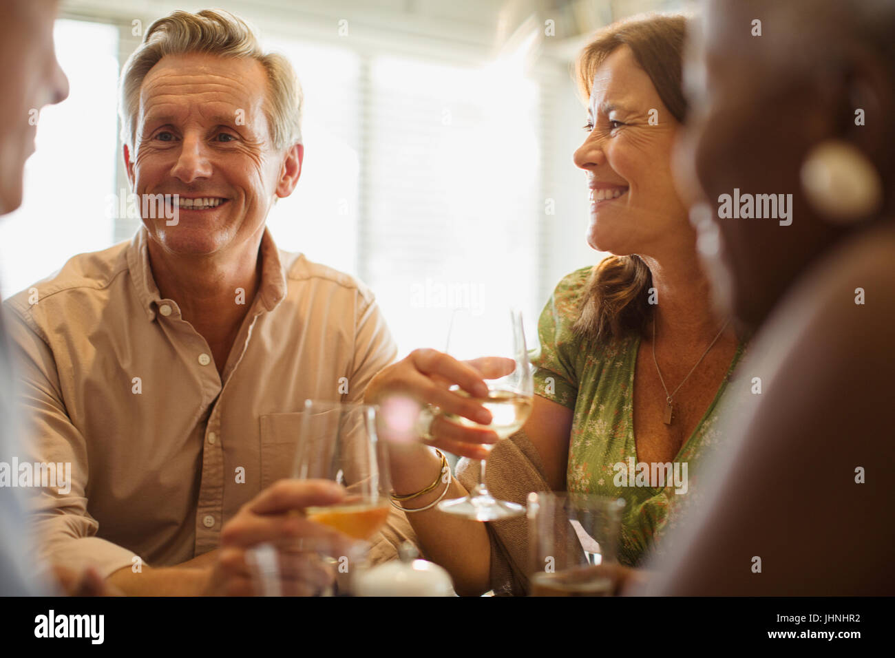 Laughing mature couple drinking wine at restaurant table - Stock Image