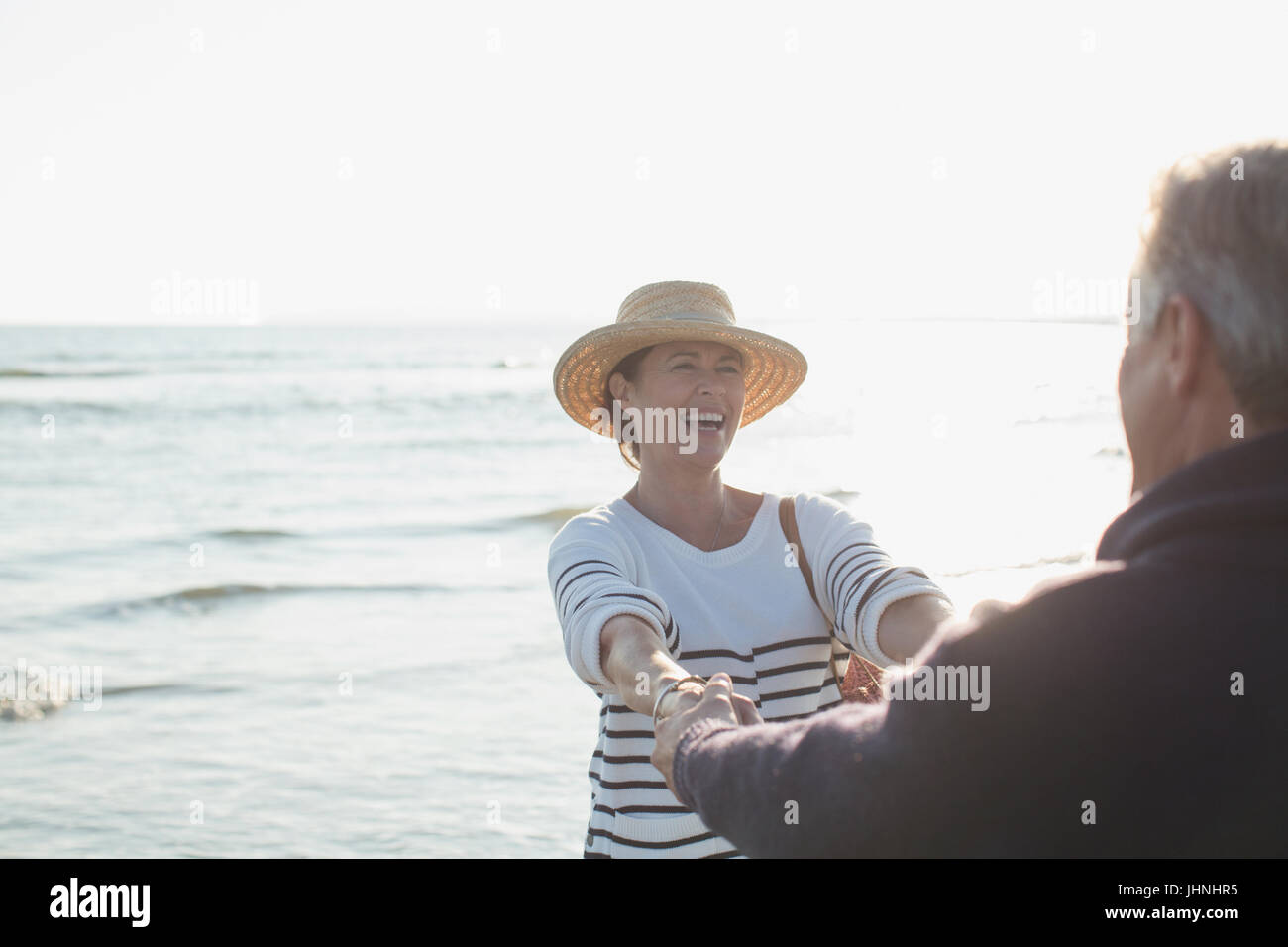 Playful mature couple holding hands on sunny ocean beach - Stock Image
