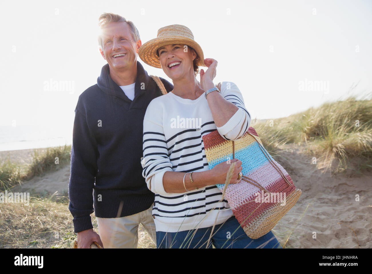 Smiling mature couple on sunny beach - Stock Image