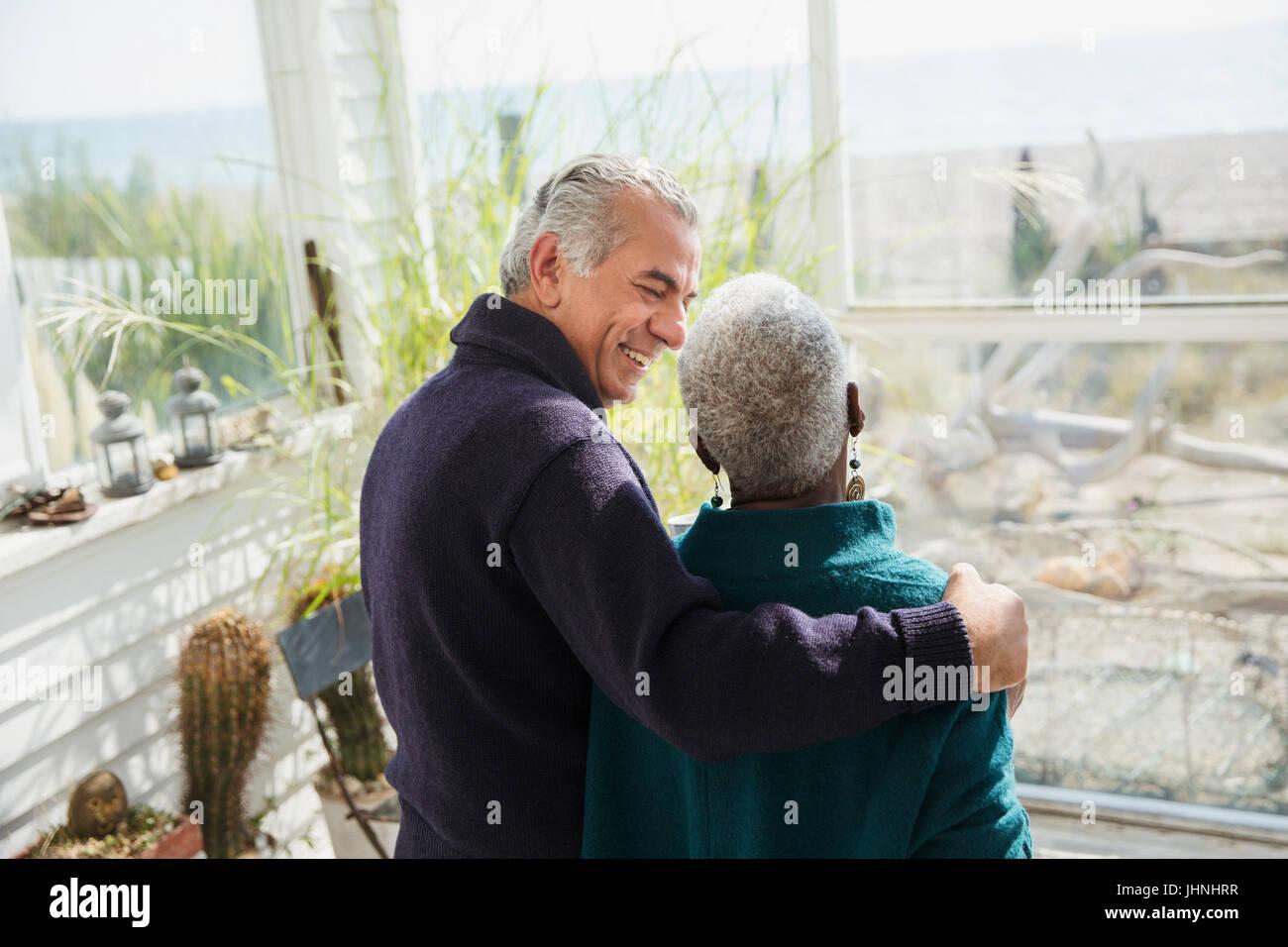 Senior couple hugging on sunny beach house sun porch - Stock Image
