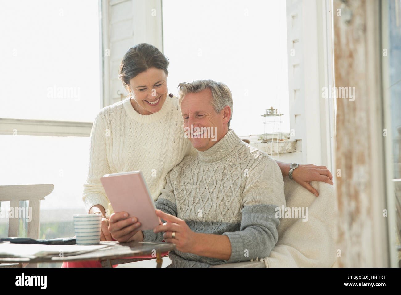 Smiling mature couple using digital tablet at table on sunny sun porch - Stock Image