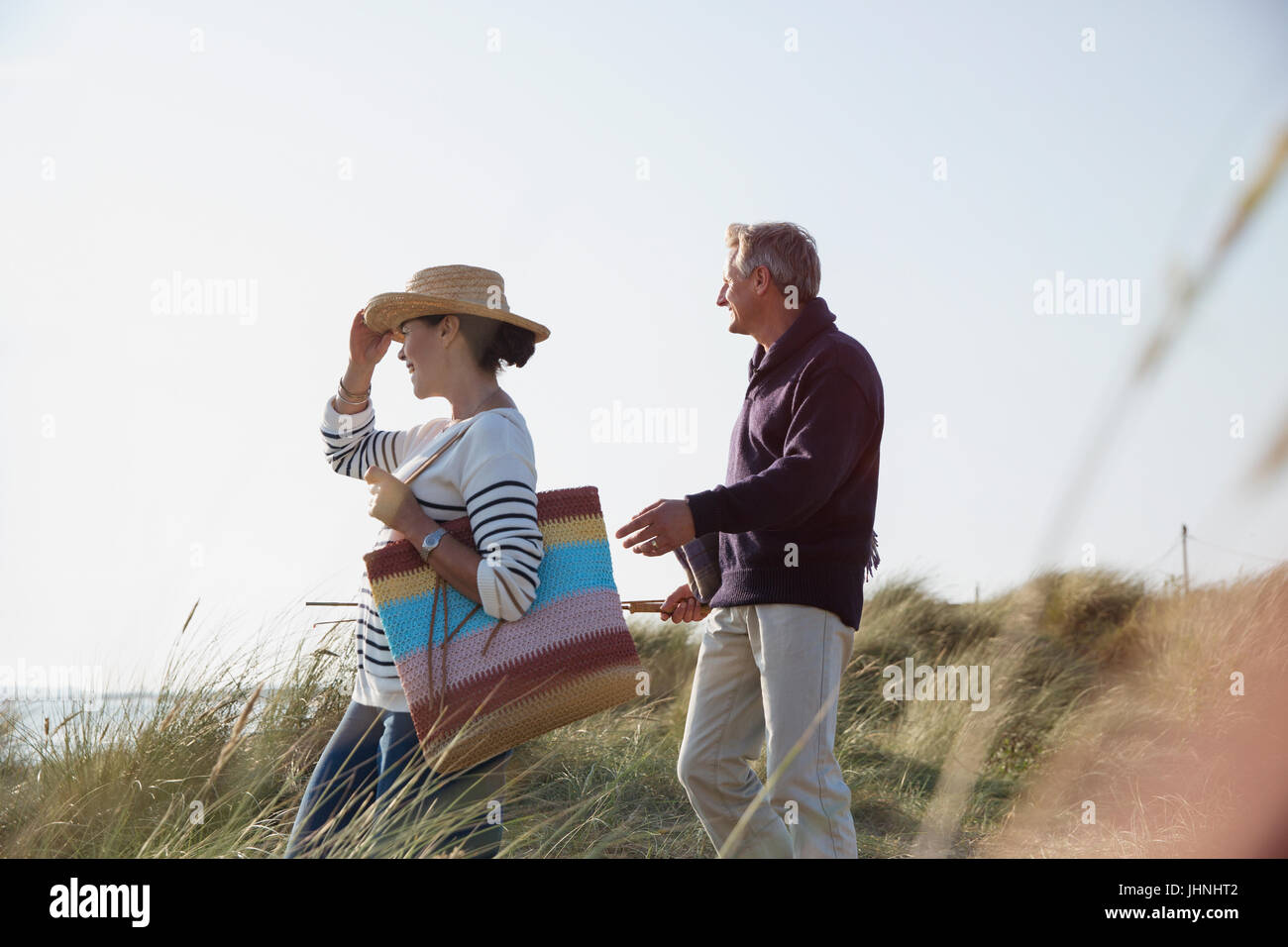 Mature couple walking on sunny beach grass path - Stock Image