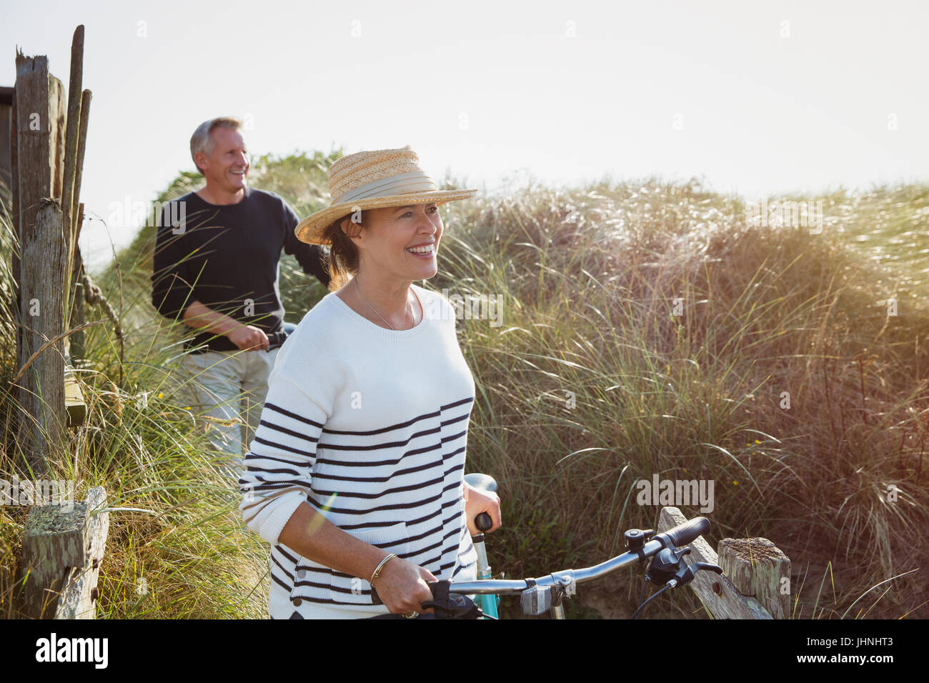 Mature couple walking bicycles along sunny beach grass - Stock Image