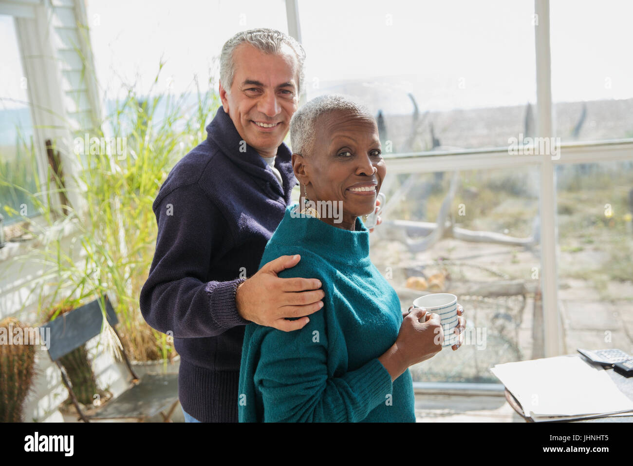 Portrait smiling senior couple hugging and drinking coffee on sunny beach house sun porch - Stock Image