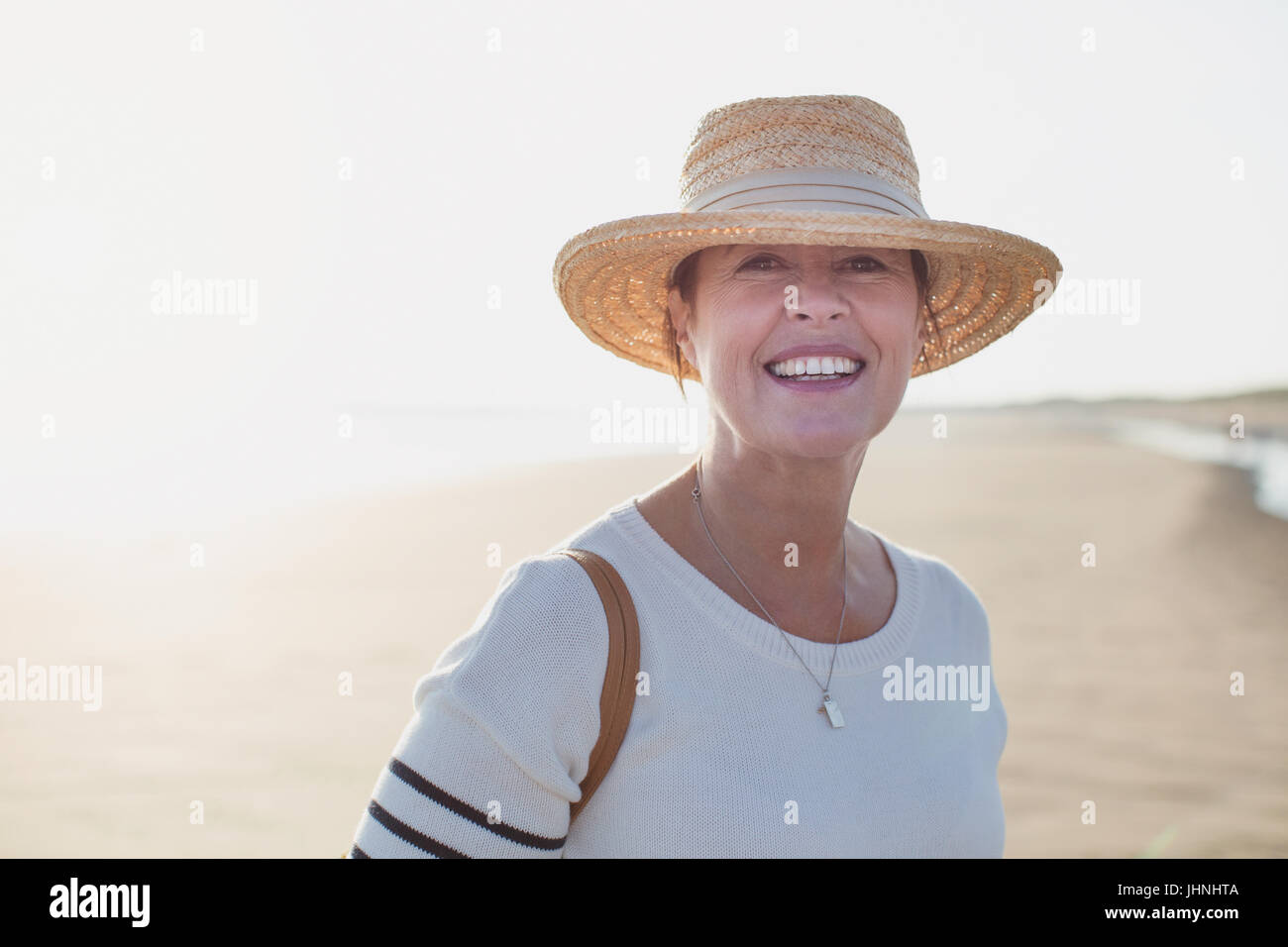 Portrait smiling mature woman wearing straw hat on sunny summer beach - Stock Image