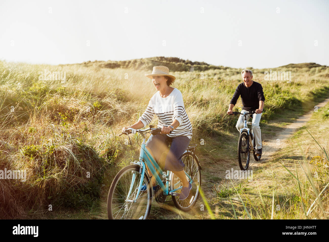 Playful mature couple riding bicycles on sunny beach grass path - Stock Image