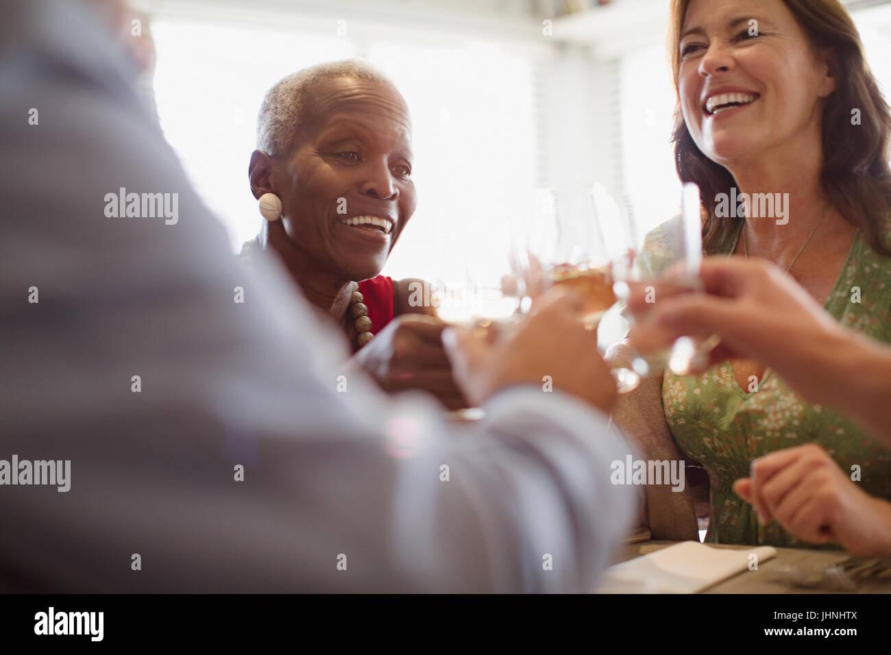 Smiling mature women drinking wine, dining at restaurant - Stock Image