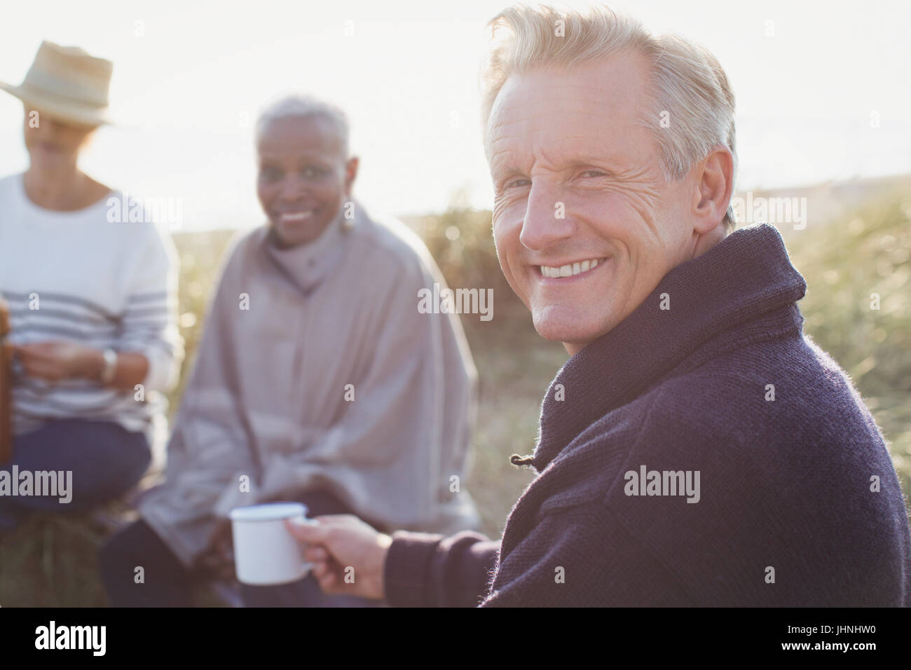 Portrait smiling senior man drinking coffee with friends on sunny beach - Stock Image