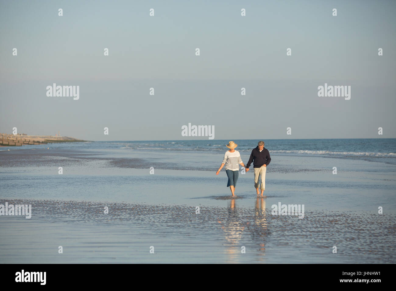 Mature couple holding hands walking in sunny ocean beach surf - Stock Image