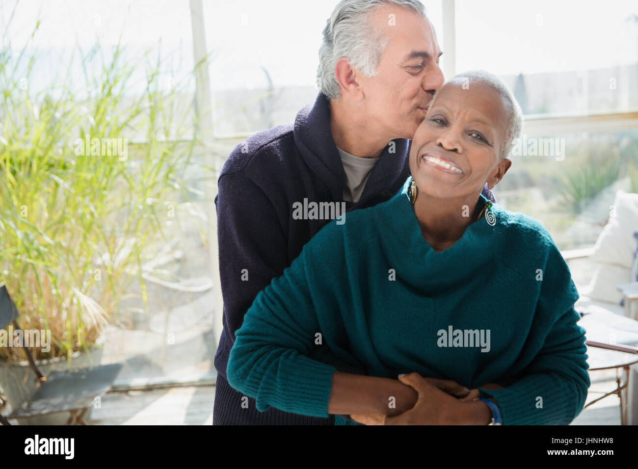 Portrait affectionate senior couple hugging and kissing Stock Photo