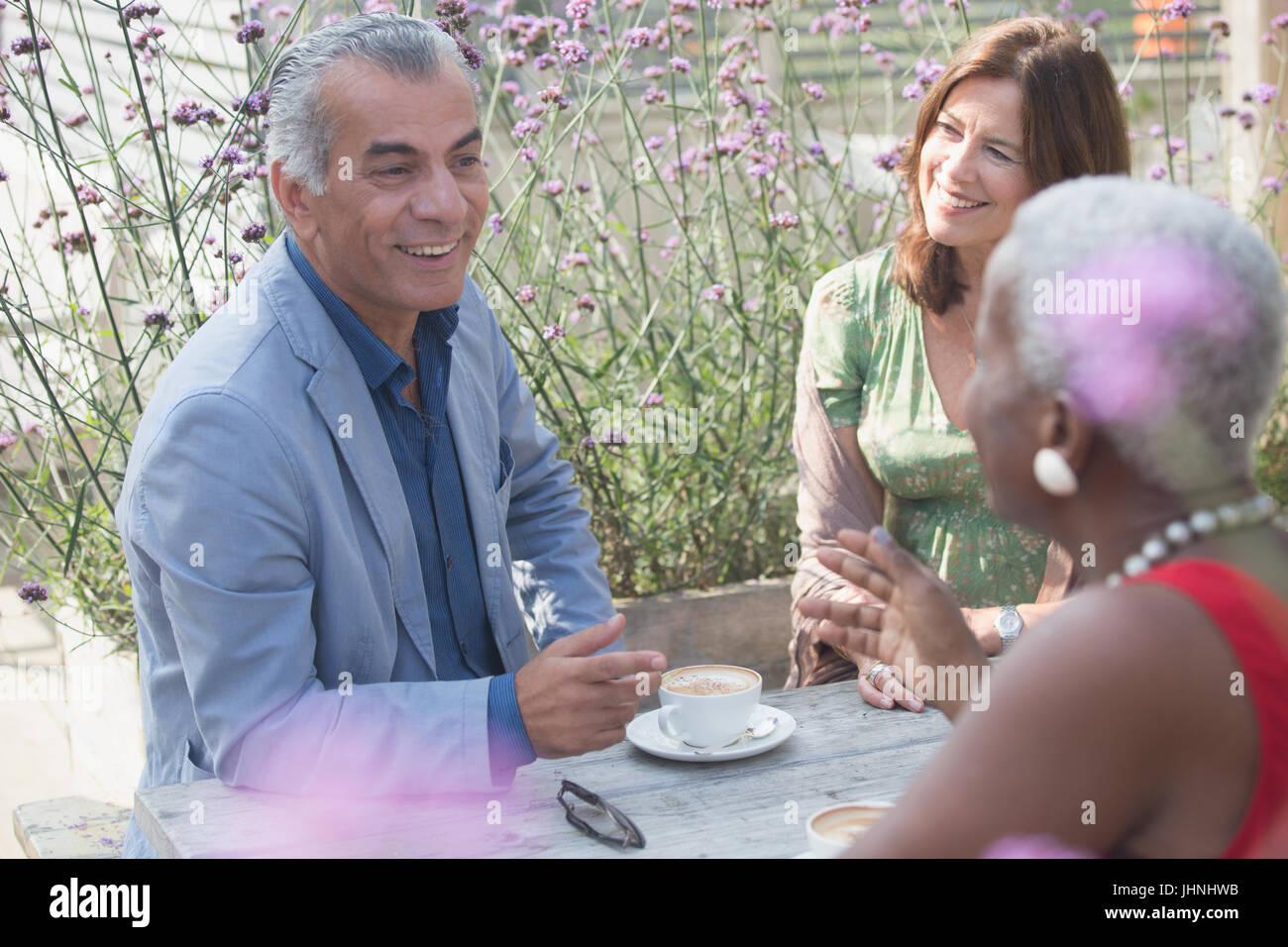 Senior friends drinking coffee on patio - Stock Image