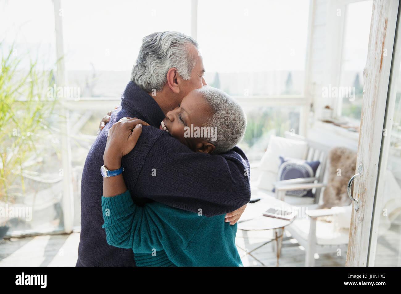 Affectionate senior couple hugging on sun porch - Stock Image
