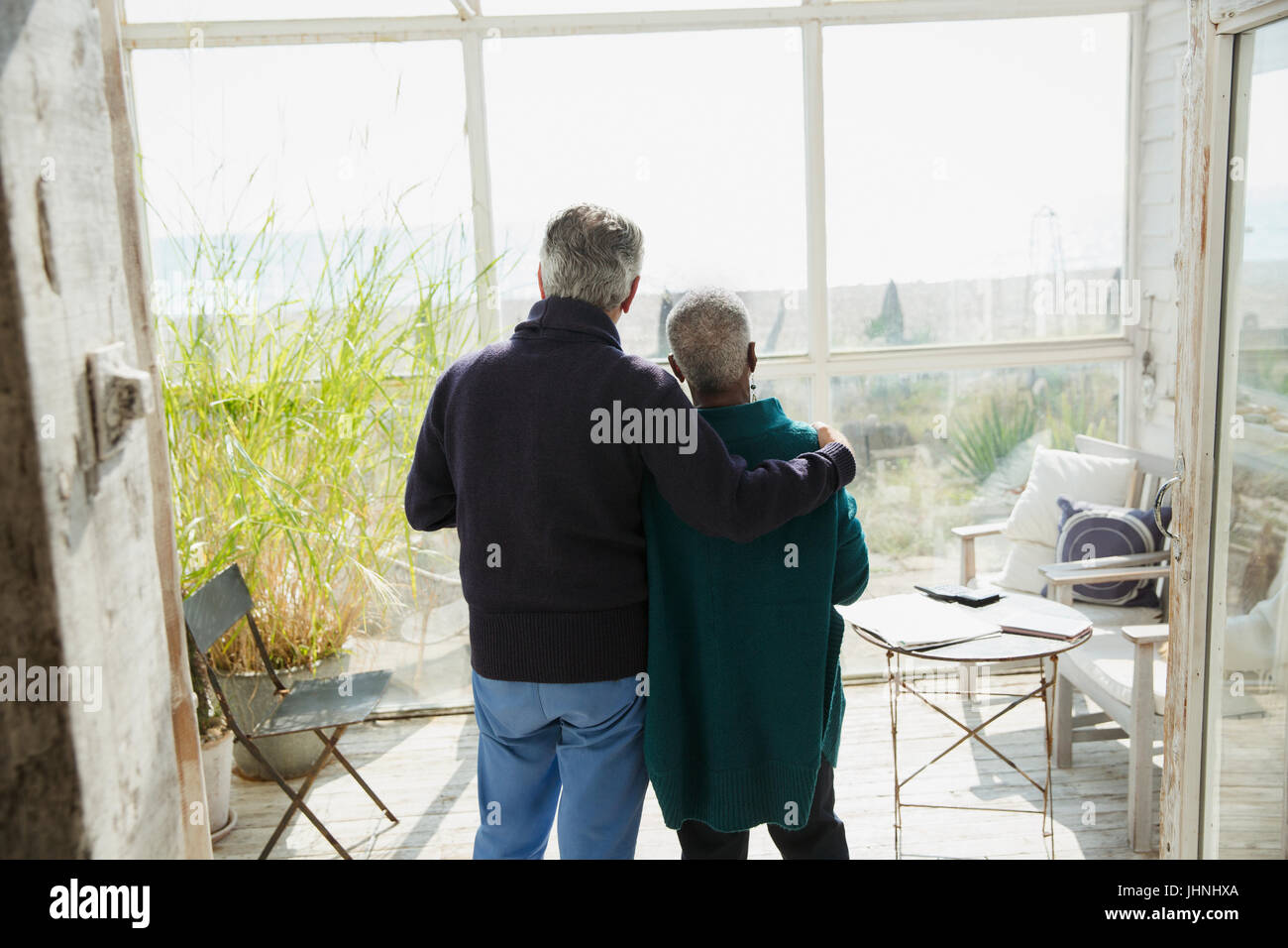 Affectionate senior couple enjoying beach view on sun porch - Stock Image