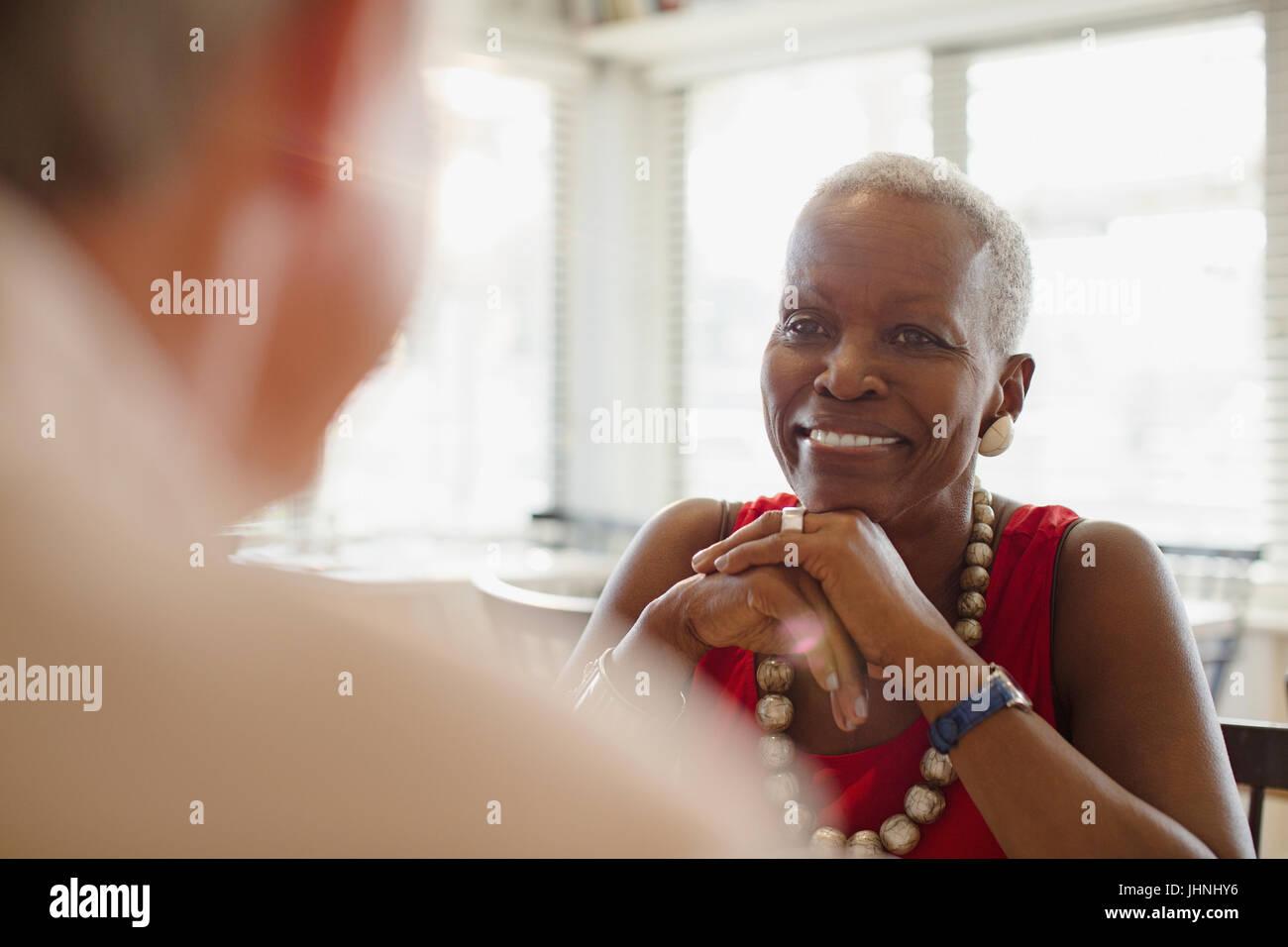 Smiling senior woman dining at restaurant - Stock Image