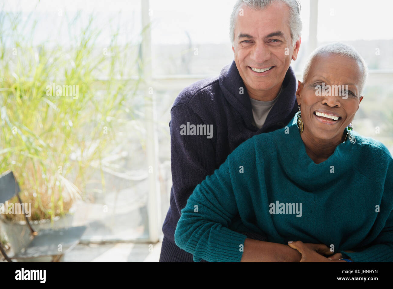 Portrait smiling senior couple hugging on sun porch - Stock Image