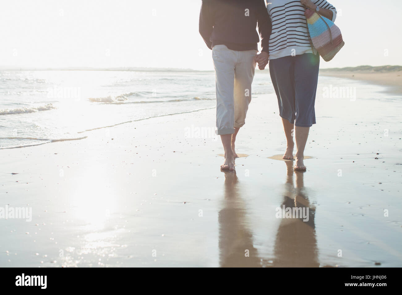 Affectionate barefoot mature couple walking, holding hands in sunny ocean beach surf - Stock Image