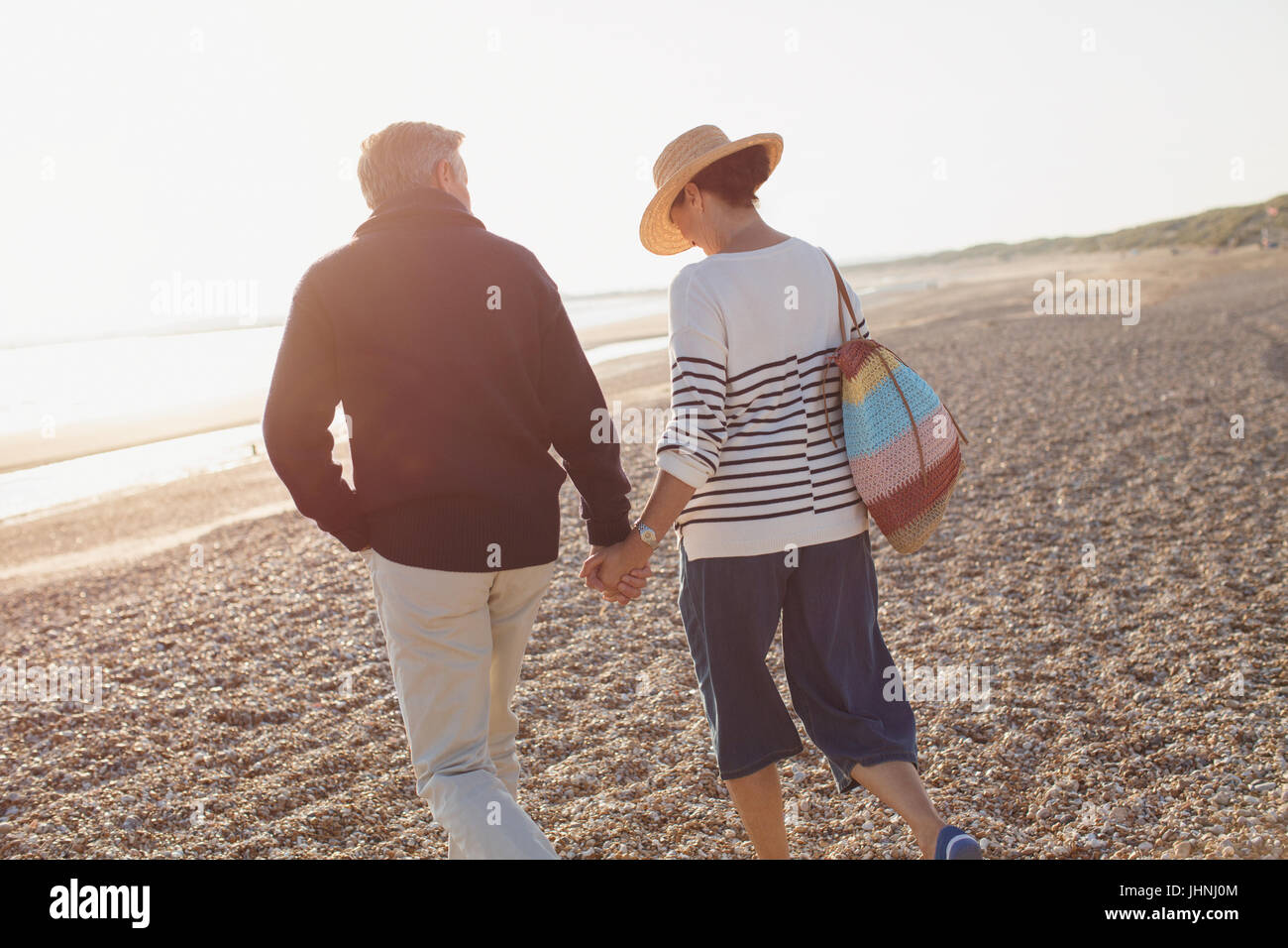Affectionate mature couple holding hands walking on sunny beach - Stock Image