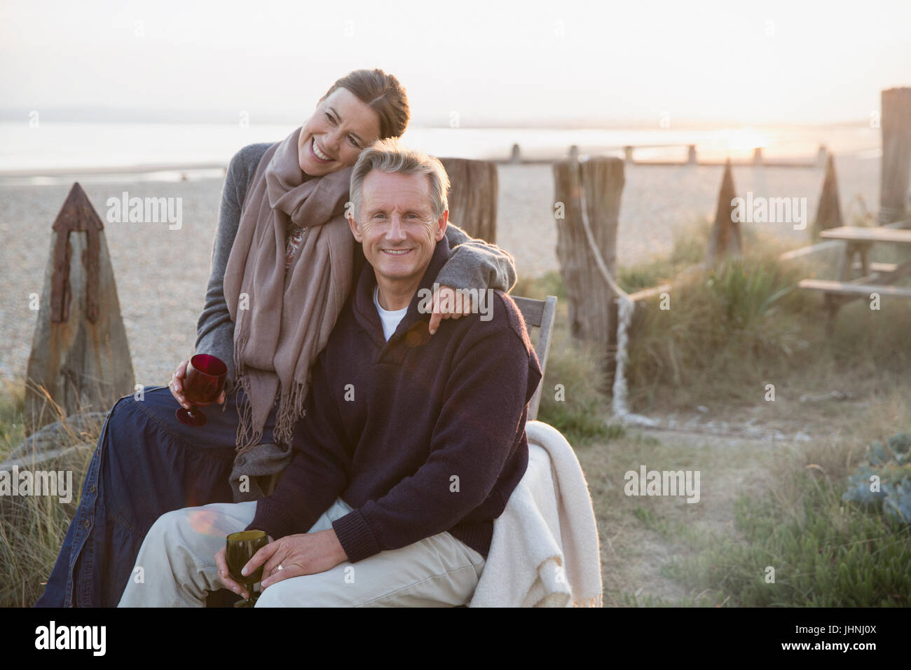 Portrait affectionate mature couple drinking wine on sunset beach - Stock Image