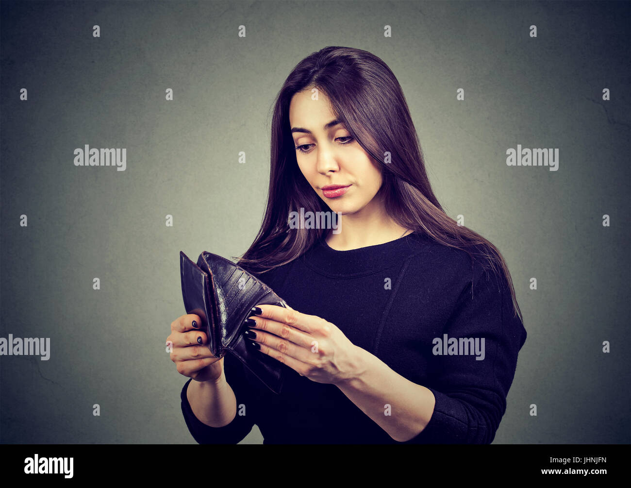 Woman with no money. Businesswoman holding empty wallet - Stock Image