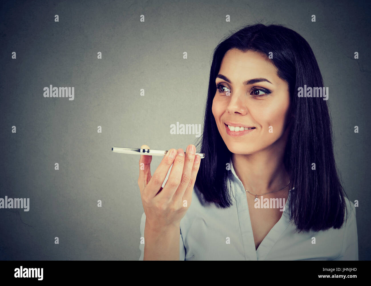 Girl using a smart phone voice recognition function on line isolated on gray wall background - Stock Image