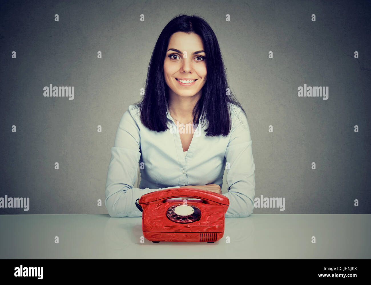 Happy woman sitting at table with vintage red telephone Stock Photo