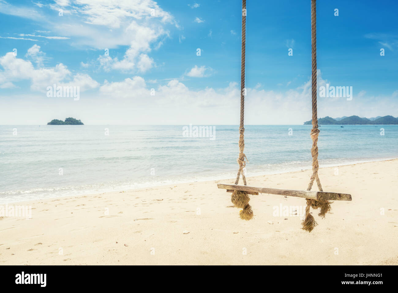 Wooden swing chair hanging on tree near beach at island in Phuket, Thailand. Summer Vacation Travel and Holiday - Stock Image