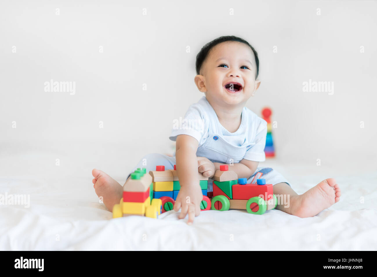 Adorable Asian baby boy 9 months sitting on bed and playing with color wooden train toys at home. - Stock Image