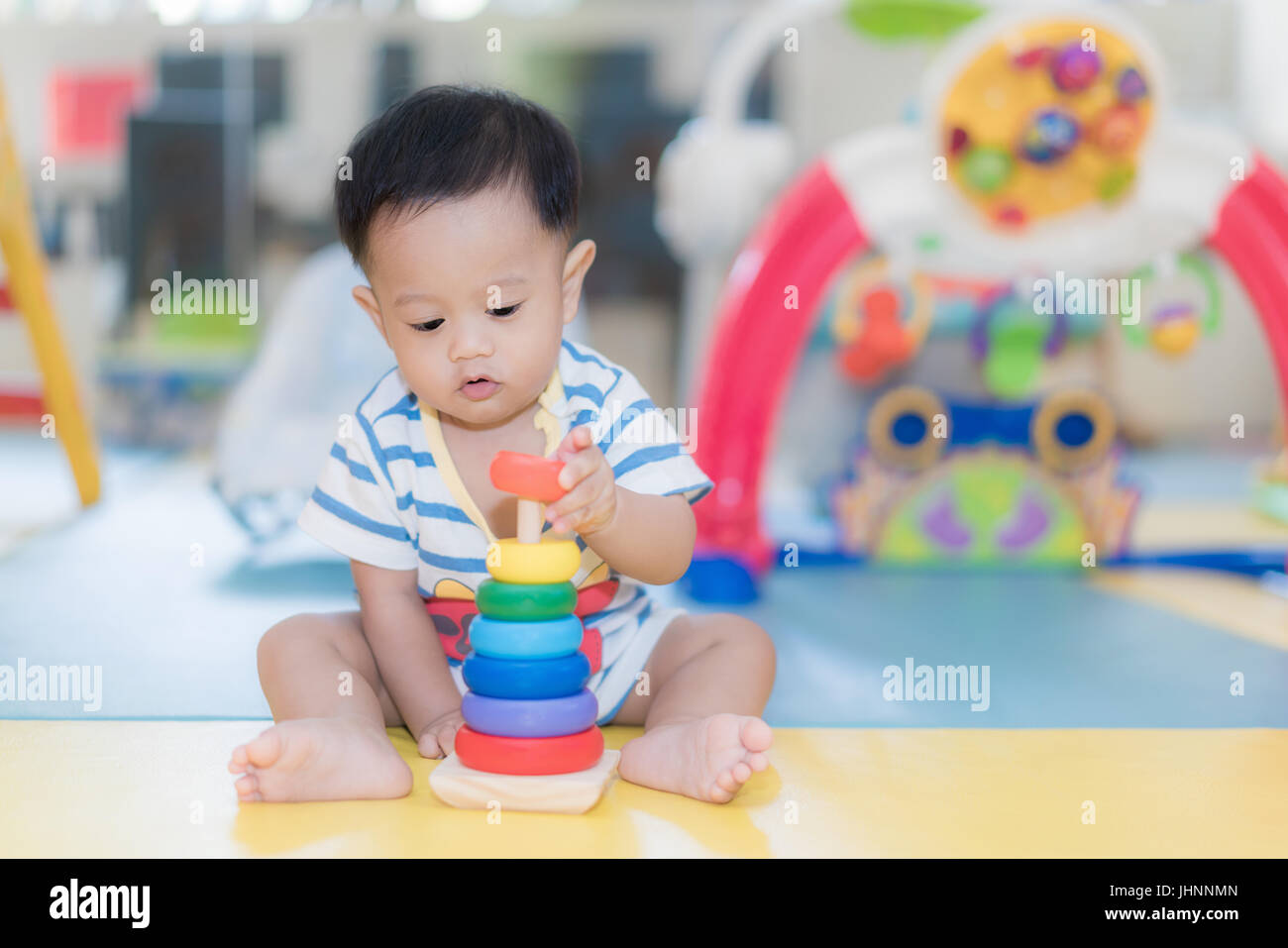 Adorable Asian baby boy 9 months sitting and playing with color developmental toys in kids room at home. - Stock Image