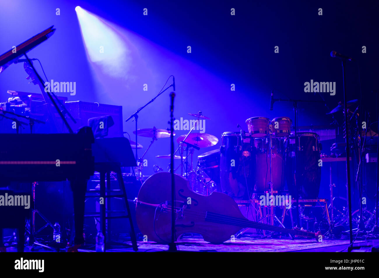 musical instruments on a stage with dramatic stage lighting - Stock Image