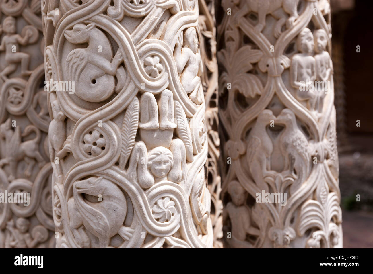 Monreale cathedral cloister carved column shaped like stylized palm stems, with figures standing, relief leaves. - Stock Image