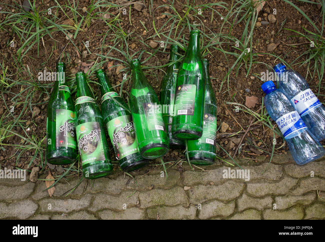 Empty Korean glass beer- and plastic water bottles lying on earth next to block-paved path. Pyongyang, DPRK / North - Stock Image