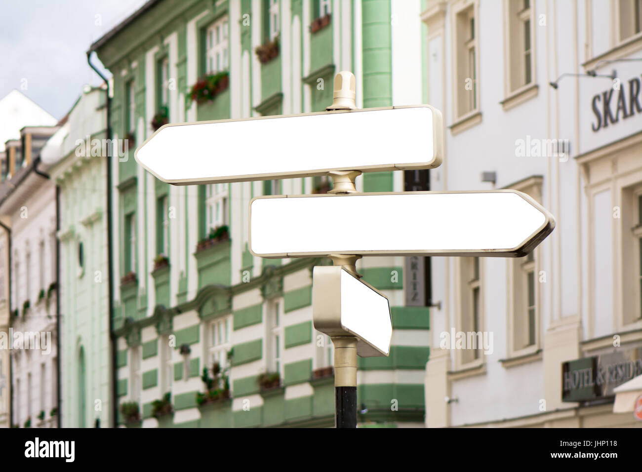 Blank guide post in the city, behind, building with classical architecture. 3 empty rectangular posters - Stock Image