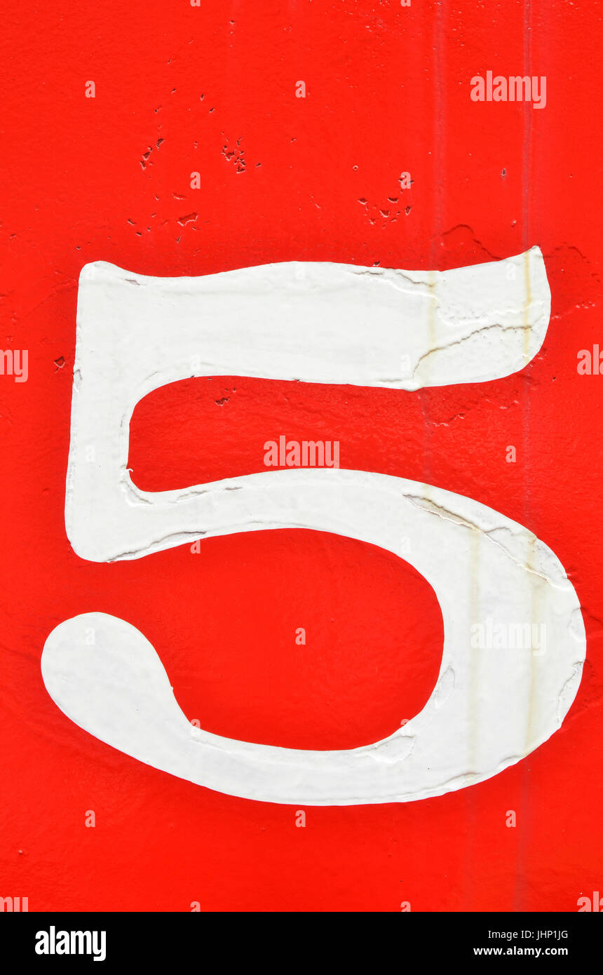 vintage hand painted mid-century numbers on red - Stock Image