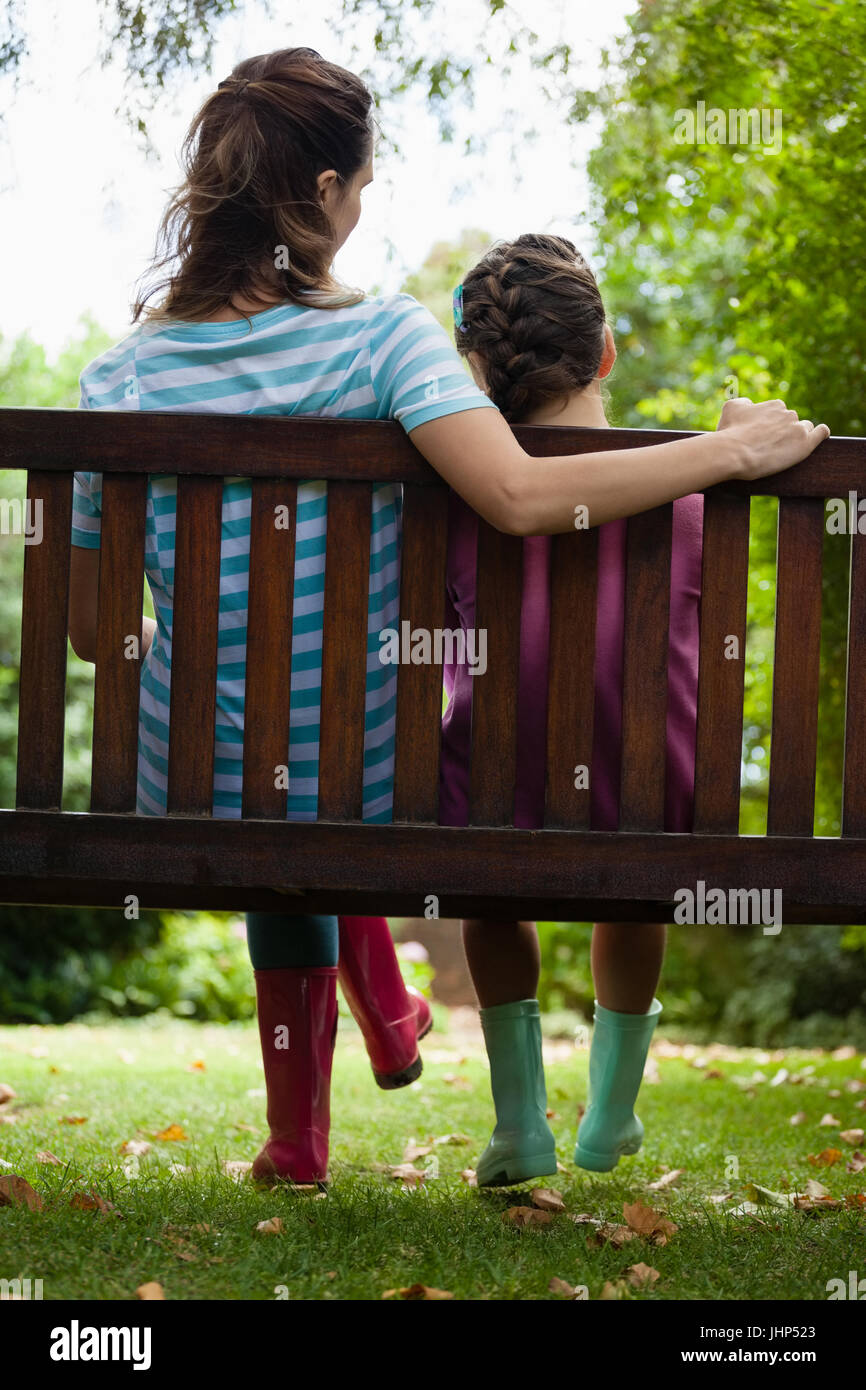 Rear view of girl and woman sitting on wooden bench at backyard - Stock Image