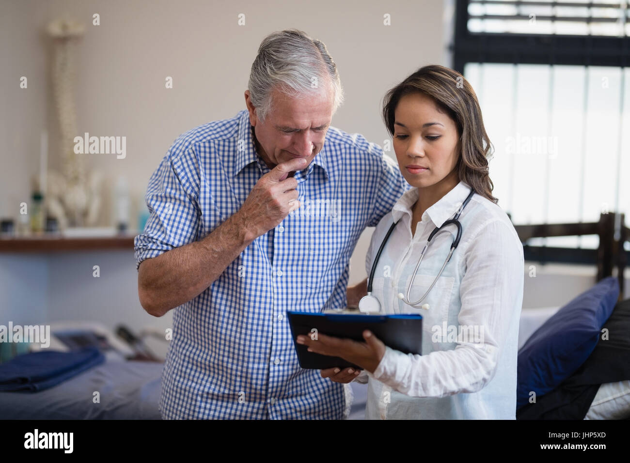 Senior male patient and female therapist discussing file at hospital ward - Stock Image