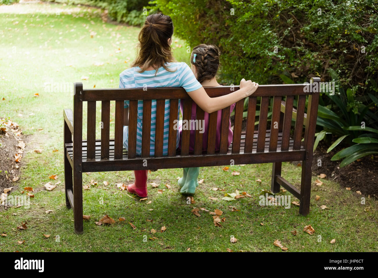 Rear view of woman and girl sitting on wooden bench at backyard - Stock Image