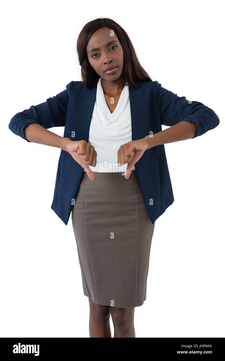 Portrait of businesswoman showing thumbs down while standing against white background - Stock Image