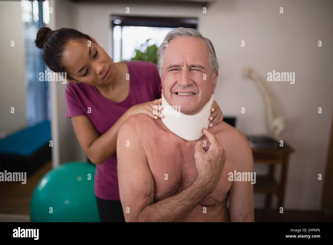 Female therapist looking at senior male patient grimacing with neck collar in hospital ward - Stock Image