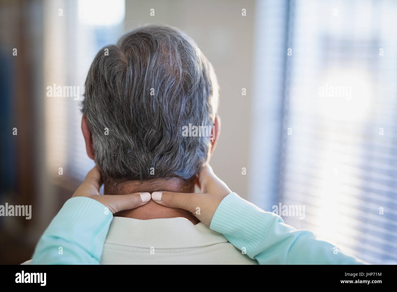 Close-up of female therapist massaging neck to male patient at hospital ward - Stock Image