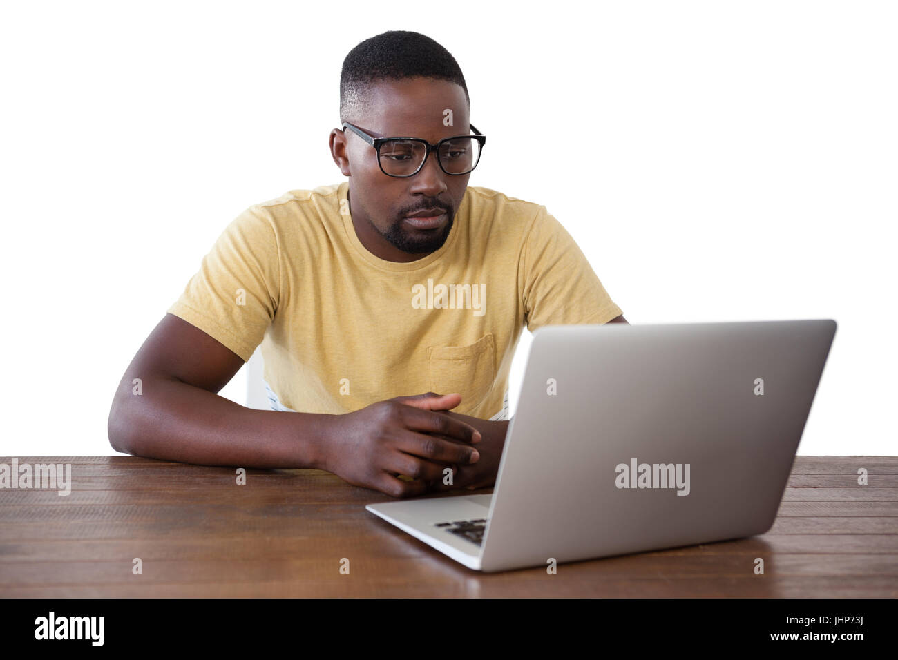 Man in spectacle using laptop against white background - Stock Image