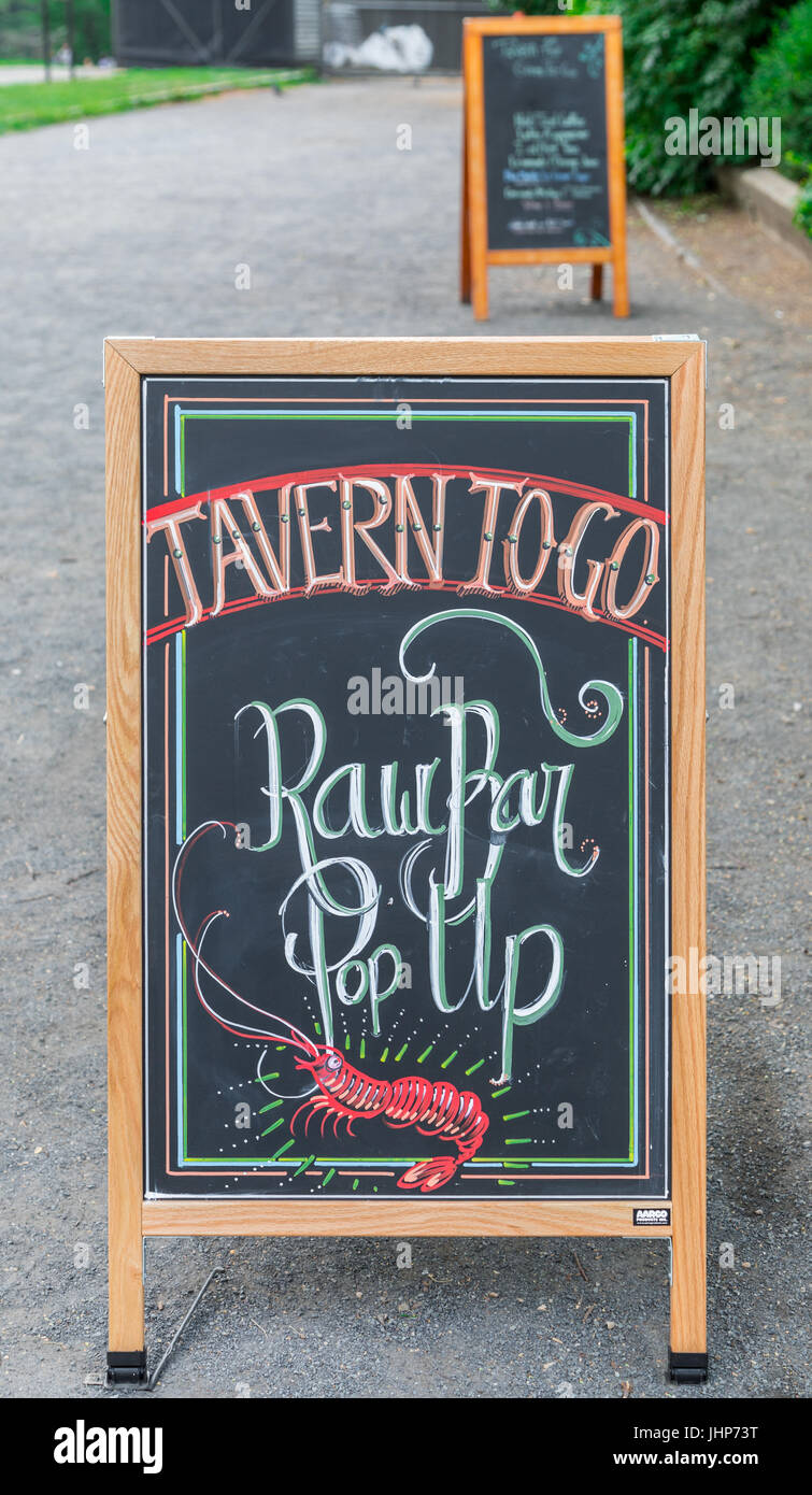 a sandwich board advertising a raw bar at tavern on the green in new york city's central park, ny - Stock Image