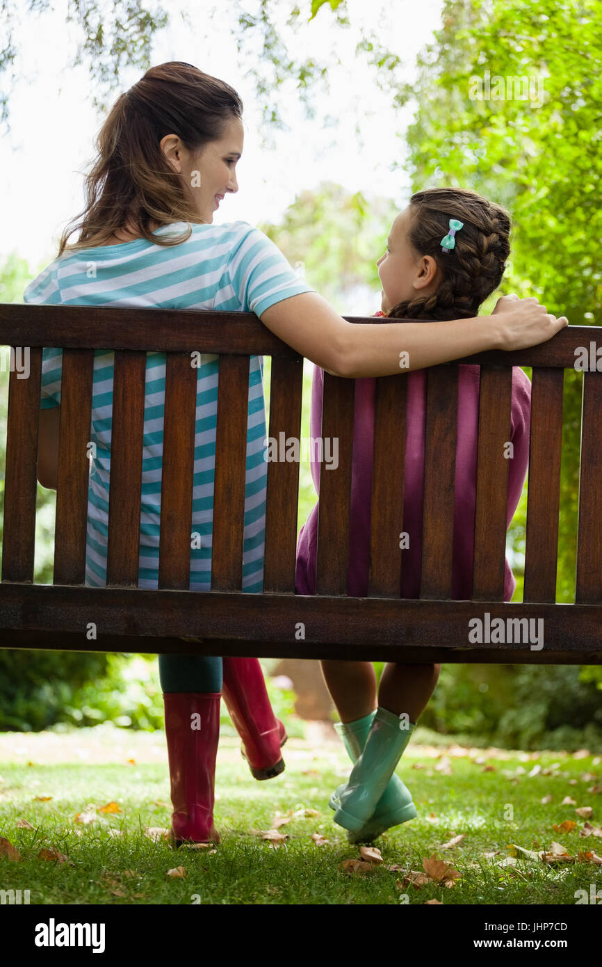Rear view of smiling woman and girl sitting on wooden bench at backyard - Stock Image