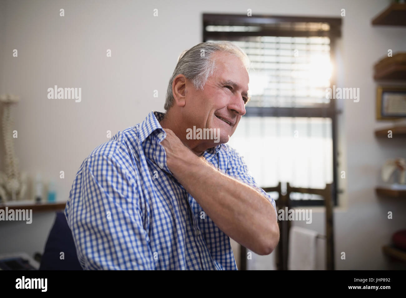 Senior male patient grimacing with neck pain at hospital ward - Stock Image