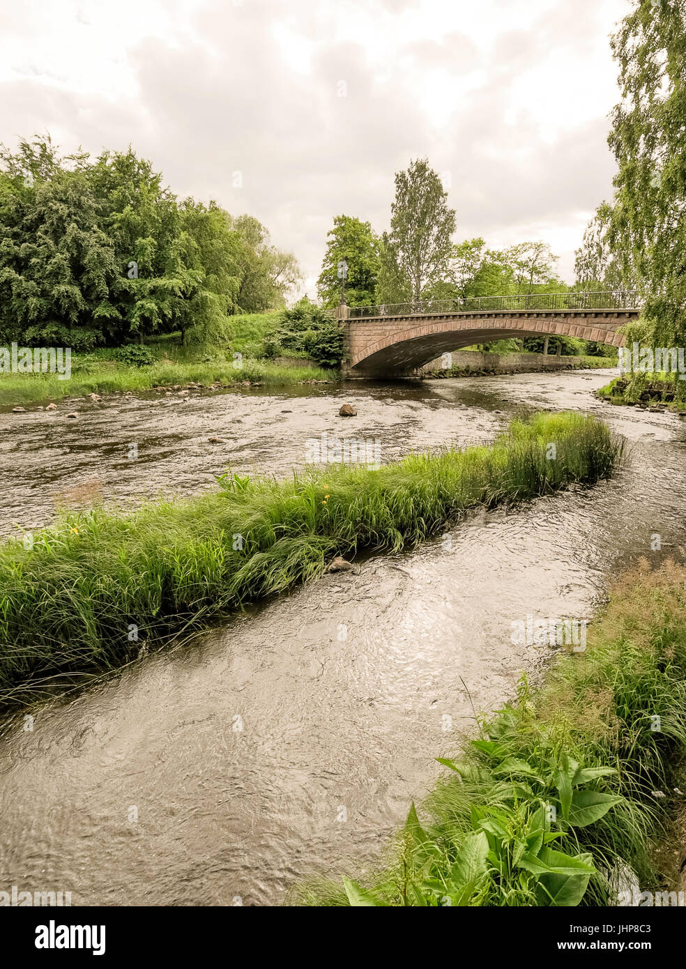 Stone Bridge over Gavle River with a cloudy sky. - Stock Image