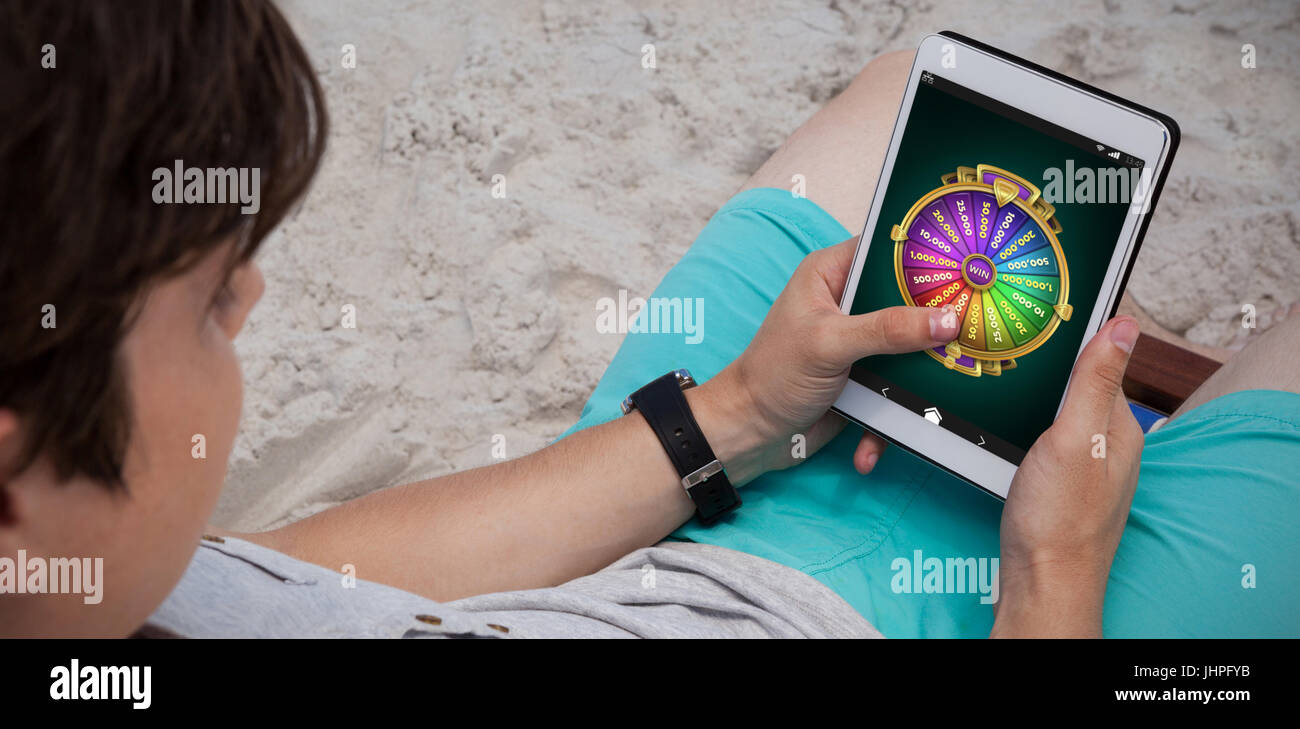Wheel of fortune on mobile display against man using digital tablet on the beach - Stock Image