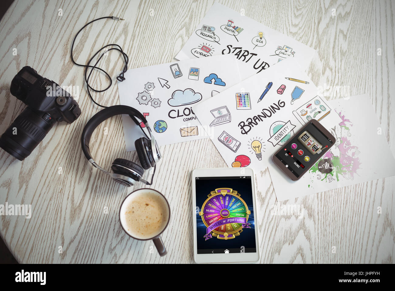 Colorful wheel of fortune on mobile display against various technologies with colorful charts and coffee on table - Stock Image