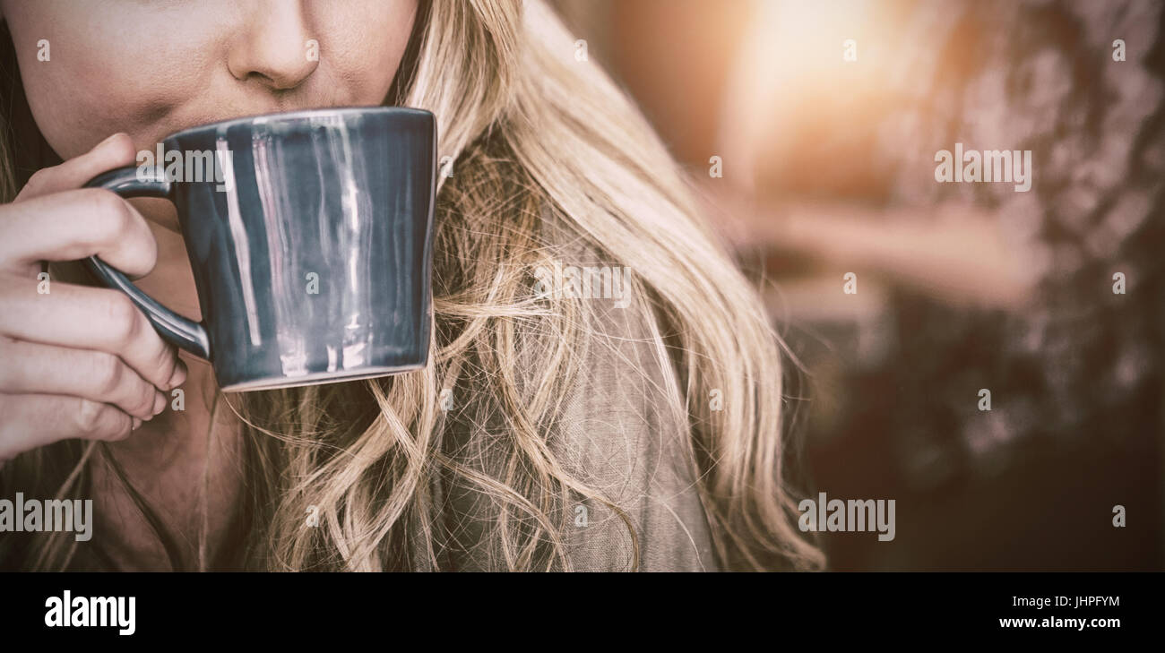 Close up of young woman drinking coffee in cafe - Stock Image
